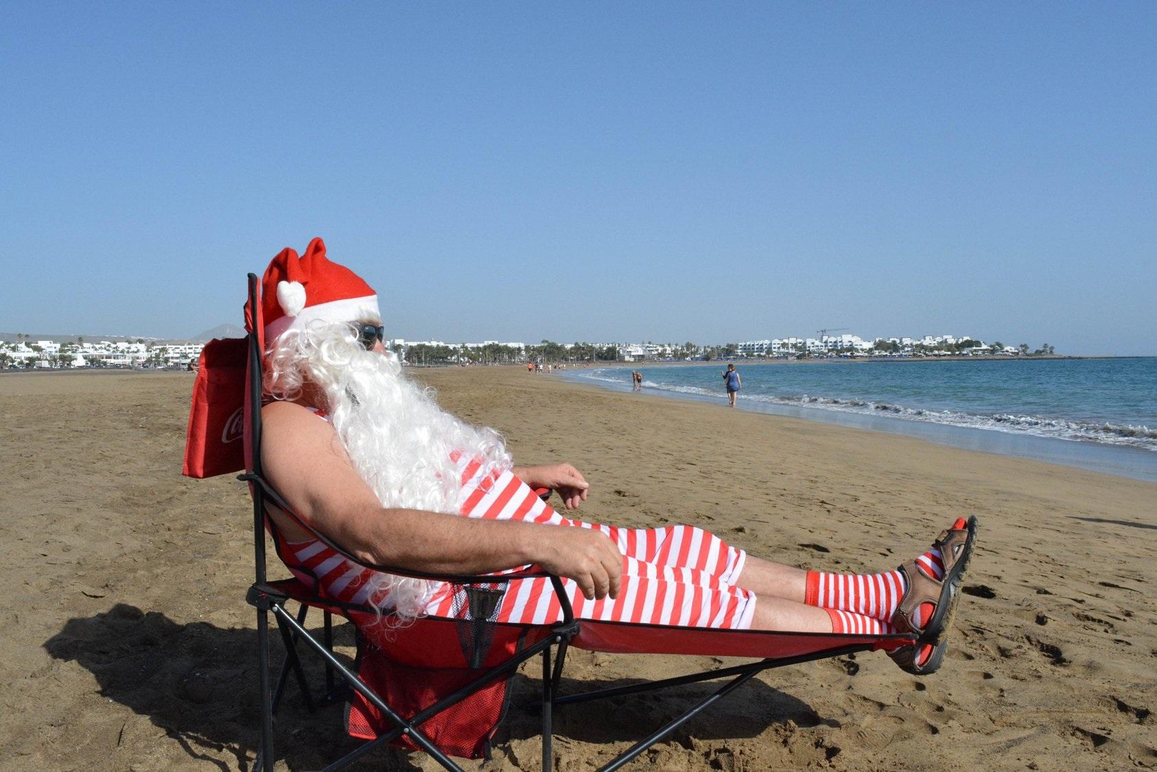 Papá Noel, de baño y  paddle surf en las playas de Puerto del Carmen